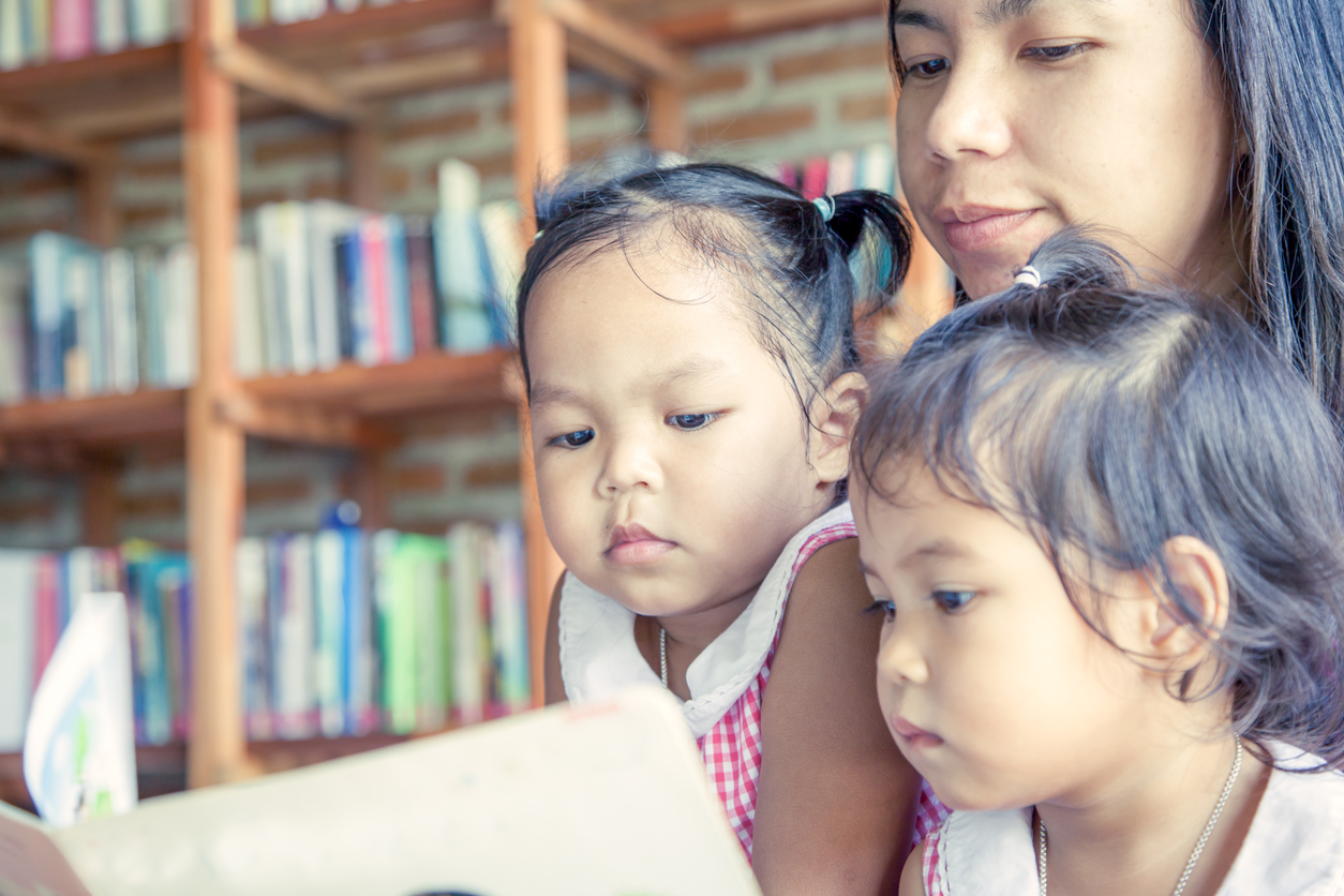 Mother and little daughter reading book together in library