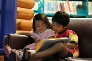 Cute children reading a book together in preschool library