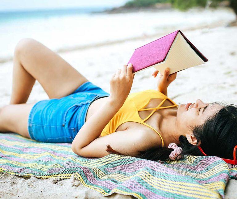 Teen girl reading on the beach