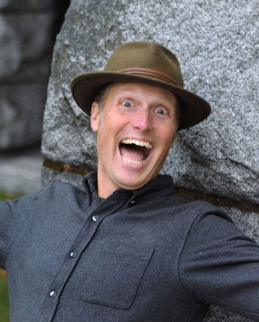 Man smiling widely in front of a rock.