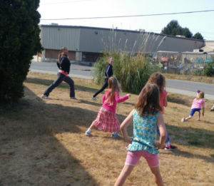 Two dance instructors are leading children in a dance class outside of the Sooke branch. In the photo they are stretching.