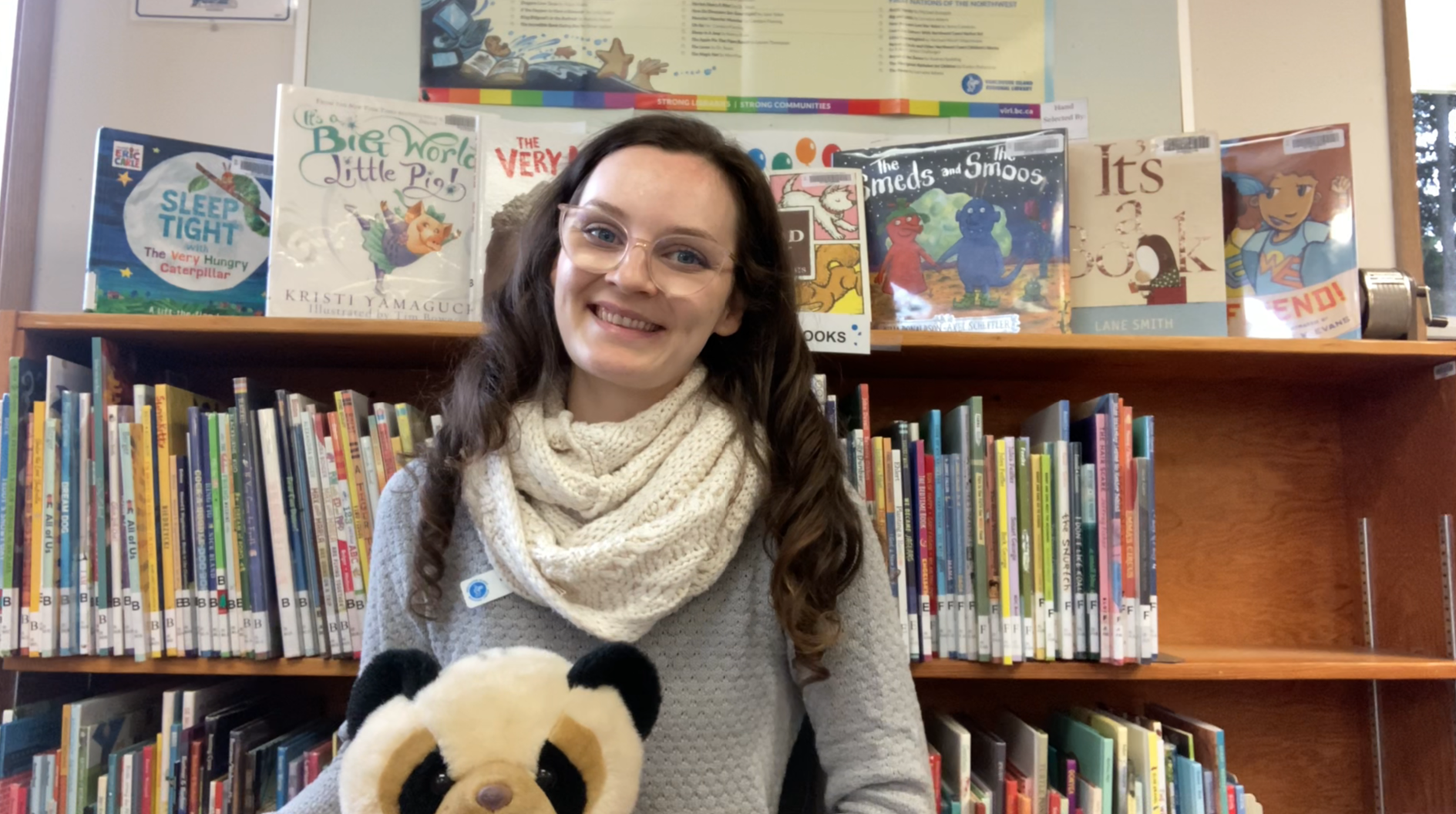 Woman sitting in front of a library bookshelf with a teddy bear on her lap.