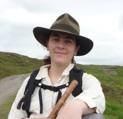 Woman standing in grassy area with wide-brimmed fedora and backpack on.